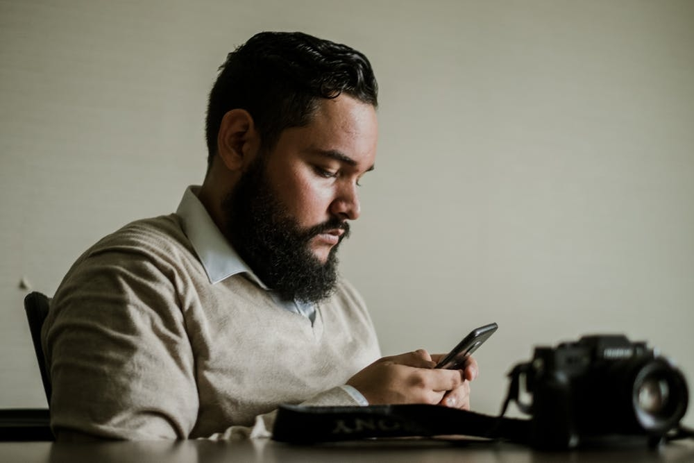 Man looking at his phone searching for mental health services near me
