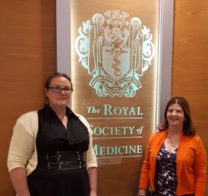 Abbey Robb and Lorraine McReight standing in front of the Royal Society of Medicine shield. Mental health news articles follow